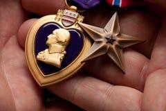 Hombre que sostiene las medallas de la guerra del corazón púrpura y del bronce Foto de archivo libre de regalías
