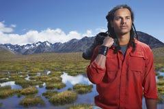 Hombre que sostiene los zapatos por la charca de la montaña Imagen de archivo