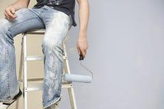 Hombre que sostiene Paintroller mientras que se sienta en la escalera de mano Foto de archivo