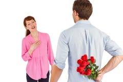 Hombre que sostiene rosas detrás de él Imágenes de archivo libres de regalías