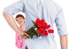 Hombre que sostiene rosas detrás de él Foto de archivo