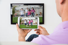 Hombre que sostiene Smartphone conectado con A TV fotos de archivo libres de regalías