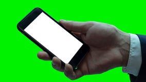 Hombre que sostiene smartphone negro con la pantalla en blanco imagen de archivo