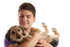Hombre que sostiene su perro Imagen de archivo libre de regalías