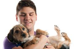 Hombre que sostiene su perro Foto de archivo
