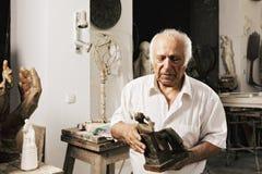 Hombre que sostiene sus ilustraciones Imagenes de archivo