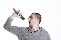 Hombre que sostiene un micrófono y que canta Fotos de archivo