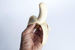 Hombre que sostiene un plátano Fotografía de archivo libre de regalías