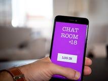 Hombre que sostiene un teléfono con la charla app imagen de archivo libre de regalías