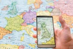 Hombre que sostiene un teléfono en un mapa Imagenes de archivo