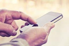 Hombre que sostiene un teléfono móvil Fotografía de archivo libre de regalías