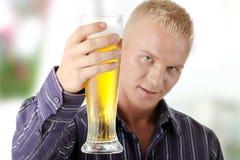 Hombre que sostiene un vidrio de cerveza Imagen de archivo libre de regalías