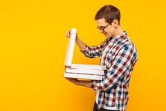 Hombre que sostiene una caja de pizza en un fondo amarillo imagen de archivo