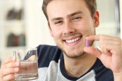 Hombre que sostiene una píldora que mira la cámara Imágenes de archivo libres de regalías