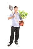 Hombre que sostiene una pala y una planta foto de archivo