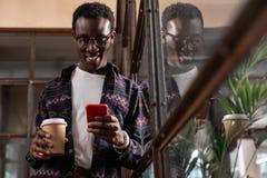 Hombre que sostiene una taza de café agarrada con la conversación que manda un SMS imágenes de archivo libres de regalías