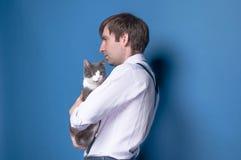 Hombre que sostiene y que abraza el gato gris foto de archivo
