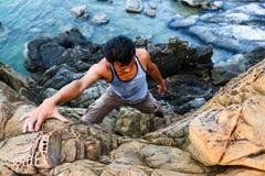 Hombre que sube las rocas cerca del mar Imagen de archivo