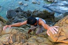 Hombre que sube las rocas cerca del mar Imágenes de archivo libres de regalías