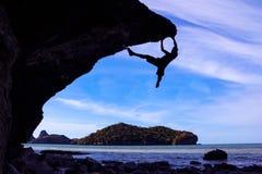 Hombre que sube las rocas en la playa Foto de archivo libre de regalías