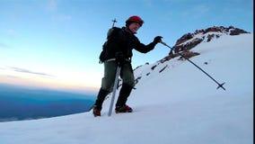 Hombre que sube para arriba el hacha de hielo de la montaña Nevado y los grampones metrajes