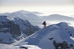 Hombre que sube un pico con el snowboard Fotografía de archivo libre de regalías