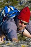 Hombre que sube una montaña Fotos de archivo libres de regalías