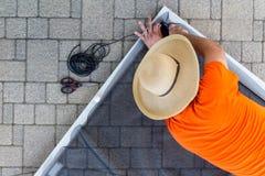Hombre que substituye la malla de alambre dañada en una puerta de malla fotos de archivo