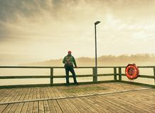 Hombre que sueña la sentada en un embarcadero de madera cerca del agua imágenes de archivo libres de regalías