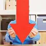 Hombre que sujeta la flecha roja grande hacia abajo Fotografía de archivo