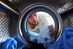 Hombre que teñe accidentalmente el lavadero dentro de la lavadora Imagen de archivo