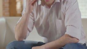 Hombre que tiene conversación sobre el teléfono móvil y que acaba la llamada, solucionando problemas almacen de metraje de vídeo