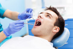 Hombre que tiene dientes examinados en los dentistas Fotos de archivo