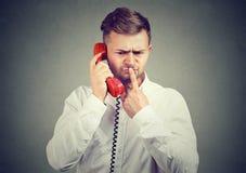 Hombre que tiene dilema durante llamada de teléfono imagenes de archivo