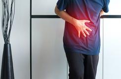 Hombre que tiene dolor de estómago doloroso en casa, sufrimiento masculino del dolor abdominal, manos que exprimen el vientre foto de archivo libre de regalías