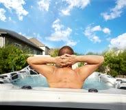 Hombre que tiene masaje en balneario de la tina caliente imagen de archivo