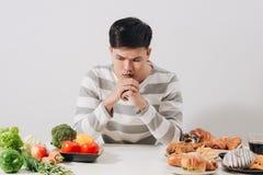 Hombre que tiene opción dura entre la comida sana y malsana imagen de archivo libre de regalías