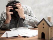 Hombre que tiene problemas financieros con la deuda y las facturas caseras, concepto del dinero , las propiedades inmobiliarias,  imagen de archivo libre de regalías