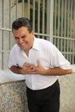 Hombre que tiene un doblez del ataque del corazón imagen de archivo