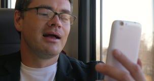 Hombre que tiene una charla video en móvil durante el tren metrajes
