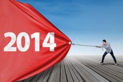 Hombre que tira de la bandera del Año Nuevo 2014 Imagenes de archivo