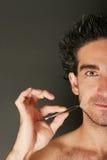 Hombre que tira de su barba Imagen de archivo libre de regalías
