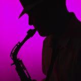 Hombre que toca el saxofón en silueta Fotos de archivo