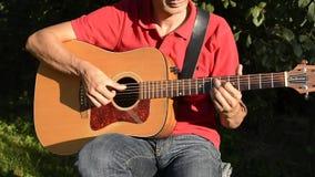 Hombre que toca la guitarra acústica al aire libre metrajes
