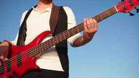 Hombre que toca la guitarra baja al aire libre metrajes