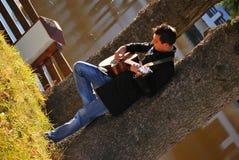 Hombre que toca la guitarra bajo árbol Fotos de archivo