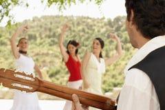 Hombre que toca la guitarra con las mujeres que bailan flamenco Imagenes de archivo