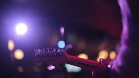 Hombre que toca la guitarra eléctrica en una etapa almacen de metraje de vídeo
