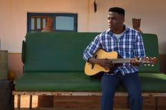 Hombre que toca la guitarra en la estación del surtidor de gasolina Imagenes de archivo