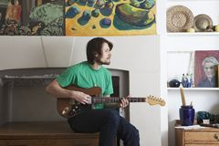 Hombre que toca la guitarra en sala de estar imagen de archivo libre de regalías